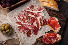 Jamon Iberico con pane bianco, olive sugli stuzzicadenti e frutta su un fondo di legno Vista superiore Fotografie Stock