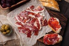Jamon Iberico met wit brood, olijven op tandenstokers en fruit op een houten achtergrond Hoogste mening stock foto's