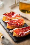 Jamon iberico tapas. Jamon iberico, the best spanish ham tapas on a slice of bread and beer Royalty Free Stock Photography