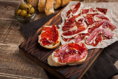 Jamon Iberico with white bread, olives on toothpicks and fruit on a wooden background. Top view.  Stock Photo