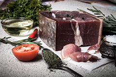Jamon med örter och kryddor, salt, olivolja och tomater på sto Arkivbild