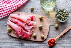 Jamon mit Kapriolen und Oliven auf dem hölzernen Brett Stockfoto