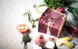 Jamon mit Kräutern und Gewürze, Salz, Olivenöl und Tomaten auf sto Lizenzfreie Stockfotos