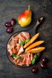 Jamon serrano或熏火腿用瓜和果子在土气木背景 意大利或西班牙开胃小菜,开胃菜板 库存图片