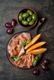 Jamon serrano或熏火腿用瓜和橄榄在土气木背景 意大利或西班牙开胃小菜 图库摄影