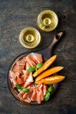 Jamon serrano或熏火腿用瓜和酒在玻璃在土气木背景 意大利或西班牙开胃小菜 免版税库存照片