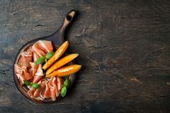 Jamon serrano或熏火腿用瓜在土气木背景 意大利或西班牙开胃小菜 库存照片