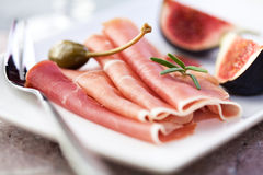 Jamon Serrano with caper berries and figs. Serrano ham with caper berries and figs Royalty Free Stock Images