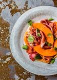 Jamon serrano prosciutto, melon and arugula salad on grey plate Royalty Free Stock Photography