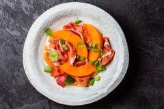 Jamon serrano prosciutto, melon and arugula salad on grey plate Royalty Free Stock Images