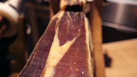 Jamon serrano.Traditional Spanish ham in the market close up.Pork leg ham on table. Gourmet Meat in restaurant interior. Whole jamon on stand stock footage