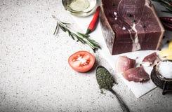 Jamon z ziele, pikantność, sól, oliwa z oliwek i pomidory na sto, Zdjęcia Stock