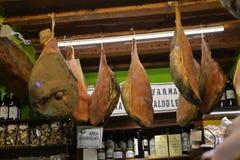 Jamones colgados en una tienda italiana Fotografía de archivo libre de regalías