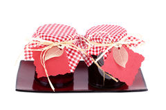 Jams. Jars of homemade jam, with gingham covers and gift tags, on ceramic tray Stock Photos