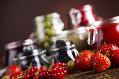 Jams in glass jars with wood and fresh berries Stock Images