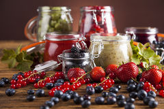 Jams in glass jars with wood and fresh berries Stock Photo