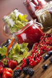 Jams in glass jars with wood and fresh berries Royalty Free Stock Photos