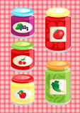 Jams and pickled vegetables. In glass jars on the background checkered tablecloth Stock Photo