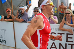 Jan Frodeno. Coming about the finish the 2014 Ironman World Championship in Kailua Kona, Hawaii. He looks happy to be finishing and placed 3rd overall Royalty Free Stock Images