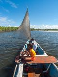 People at boat in Real river, Brazil. Jandaíra, Bahia/ Brazil - July 3, 2005. Kids inside small sail boat at Real river, Bahia, Brazil, close to Mangue Seco stock photography