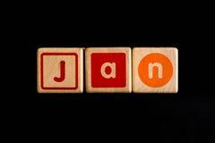janeiro em cúbico de madeira no fundo preto Fotos de Stock