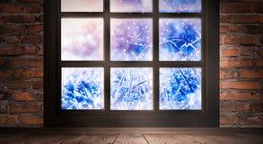 A janela é congelada, manhã gelado, flocos de neve no vidro, uma sala vazia com uma janela, uma parede de tijolo velha e um assoa imagens de stock royalty free