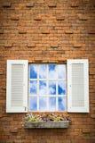 Janela aberta com a cesta da flor na parede de tijolo Fotos de Stock Royalty Free