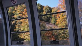 Janela aberta da cabine do teleférico em árvores do outono na inclinação de montanha filme