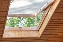 Janela aberta do telhado com cortinas ou cortina no sótão de madeira da casa Sala com o teto inclinado feito de materiais naturai imagem de stock royalty free