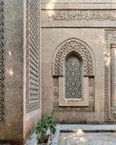 Janela arqueada com grade do teste padrão geométrico de mármore ornamentado uma parede de pedra dos tijolos Foto de Stock