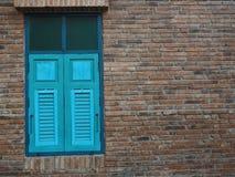 Janela azul feita de madeira na parede de tijolo velha imagem de stock