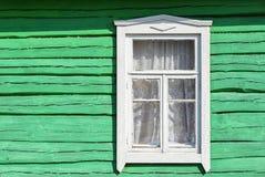 Janela branca na parede verde de uma casa de madeira velha imagem de stock