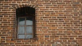 Janela coberta com a malha do metal, parede de tijolo antiga da prisão medieval, captiveiro video estoque