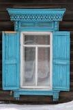 A janela com a arquitrave cinzelada de madeira na casa de madeira velha na cidade velha do russo imagem de stock royalty free