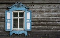A janela com a arquitrave cinzelada de madeira na casa de madeira velha na cidade velha do russo fotos de stock