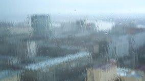 A janela com chuva do gotejamento deixa cair o close-up com uma cidade obscura no fundo vídeos de arquivo