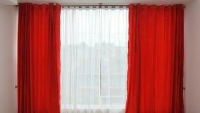 A janela com cortinas vermelhas abre Fotos de Stock