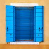 Janela com o obturador azul fechado na parede amarela Italy, Veneza, Burano Imagens de Stock Royalty Free