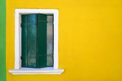 Janela com o obturador verde fechado na parede amarela Italy, Veneza, Burano Foto de Stock