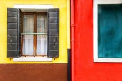 A janela com obturadores abre em um fundo amarelo e vermelho da parede Copie o espaço Fotos de Stock