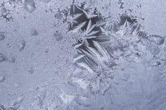 Janela congelada com teste padrão gelado branco de flocos de neve aguçado e de gotas congeladas fotos de stock