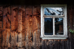 A janela da casa de log de madeira velha no fundo da madeira Fotografia de Stock Royalty Free