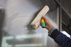 Janela da limpeza da mão de uma construção imagens de stock