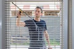 Janela da limpeza do homem de uma casa imagens de stock