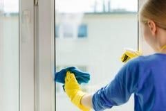 Janela da limpeza da menina em casa que usa o pano detergente Imagens de Stock Royalty Free