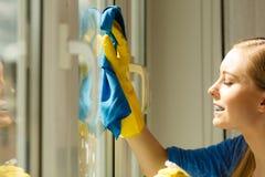 Janela da limpeza da menina em casa que usa o pano detergente foto de stock