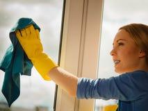 Janela da limpeza da menina em casa que usa o pano detergente imagem de stock