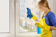 Janela da limpeza da mulher em casa imagem de stock