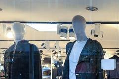 Janela da loja com roupa exterior da cor preta em manequins claros fotos de stock royalty free