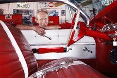 Janela de Leaning Over Car do mecânico na garagem fotos de stock royalty free